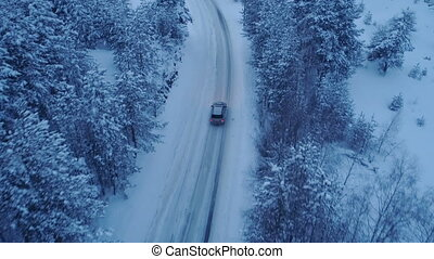 Silver car driving on winter country road in snowy forest