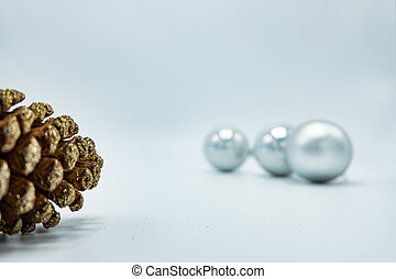 Silver Christmas balls on white background with pine cone.