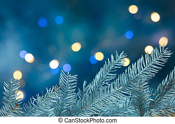 christmas tree branches on blurred blue holiday background with lights