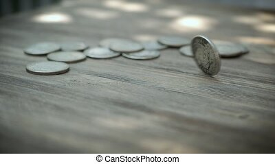 Silver Coin Rotating on a Wooden Table. Spinning American Dollars Coin.