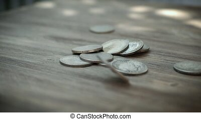 Silver coins falling in slow motion on a table. Slowmo American Dollars Falling Down