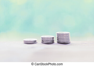 Silver coins on wooden table with pastel blurred background, saving money concept