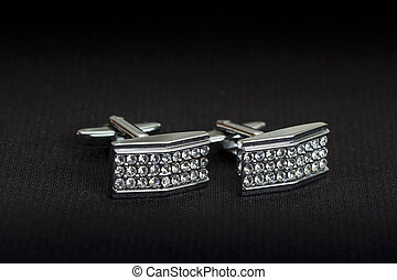 Pair of silver cuff links over black background