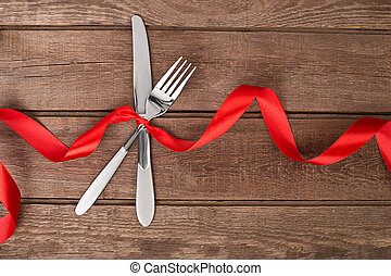 silver cutlery, fork and knife table setting on old rustic wooden background.