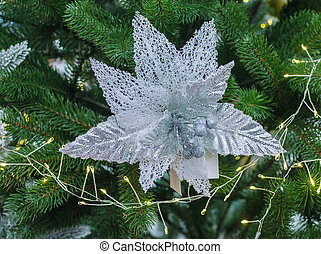 silver decoration in the form of a flower on a Christmas tree