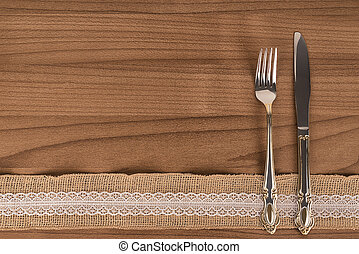Silver fork and kitchen knife on wooden table. Eat concept flat lay, top view.