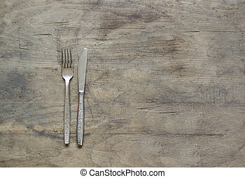Silver fork and knife on old, rusty, wooden background