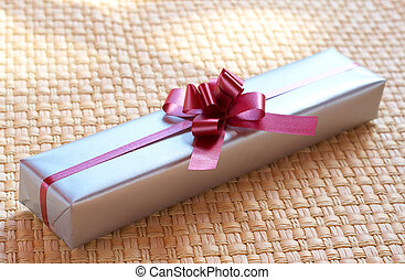 Silver gift box with pink bow on woven straw background