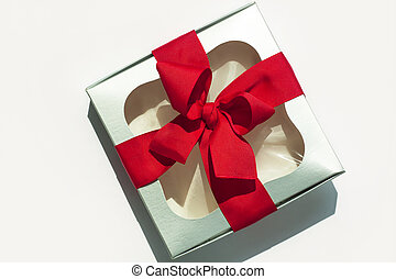 Silver gift box with red ribbon bow isolated on white background. Copy space, flatlay, top view.
