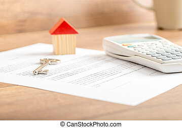 Silver house key lying on a contract for house sale, lease,...