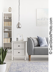Silver lamp above cabinet next to grey sofa in white living room interior with bookshelf. Real photo