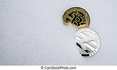 Silver Litecoin and gold bitcoin cryptocurrency on snow. The concept of freelancing, the stock exchange. Gold bitcoin on cold winter snow background. Frozen bitcoin. Frozen account.
