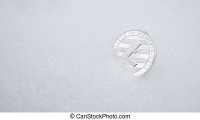 Silver Litecoin cryptocurrency on snow, in the background. The concept of freelancing, the stock exchange. Gold bitcoin on cold winter snow background. Frozen bitcoin. Frozen account.