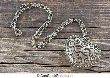 Silver necklace with heart pendant on wooden background
