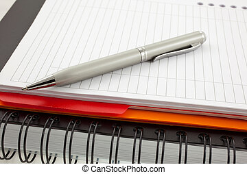 silver pen and two paper notebooks: orange and black