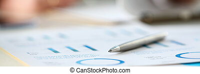 Silver pen lie at important paper on table in office