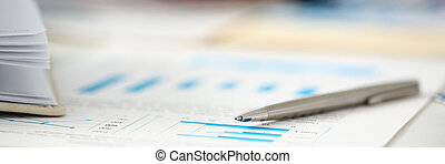 Silver pen lie on important paper at table with group of colleagues in background