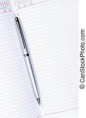 silver pen on notebook vertical