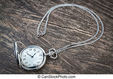 Silver pocket watch on chain, a wooden texture.