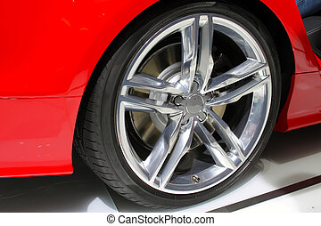 Silver rim and tire of a red car