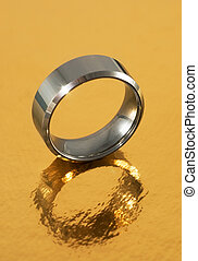 Silver ring reflected in golden surface