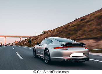 Silver sedan on the mountain roads, extreme motion, view from behind