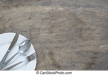 Silver spoon, fork and knive in plate on old, rusty, wooden background