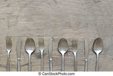 Silver spoons, forks and knives on old, rusty, wooden background