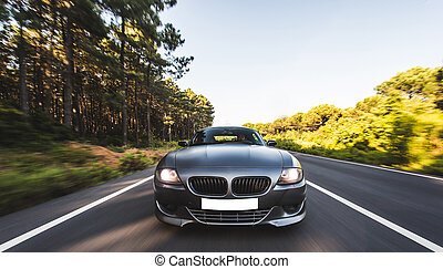 Silver sport cabriolet with yellow lights on in the forest road