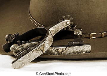 Silver Spurs and a Cowboy Hat - Western themed close-up of...
