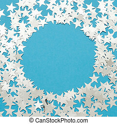 Silver star glitter on blue pastel background.
