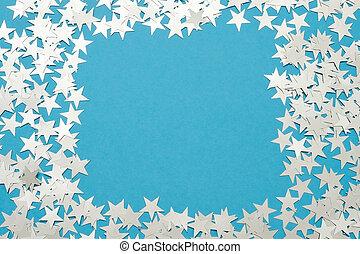 Silver star glitter on blue pastel background.
