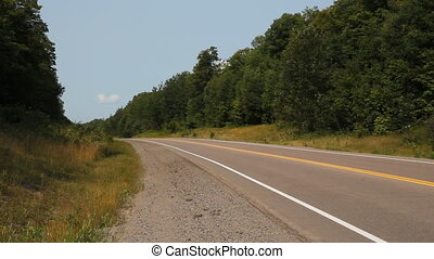 Silver SUV passing on Highway 118 in Haliburton County, Ontario, Canada.