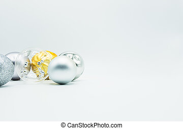 Silver, transparent and golden christmas balls on white background.