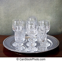 Silver tray with crystal glasses on a grunge background