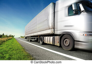 Silver truck driving on country road/motion blur