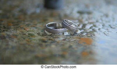 silver wedding rings on rain