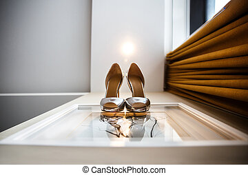 Silver wedding shoes on the white wall