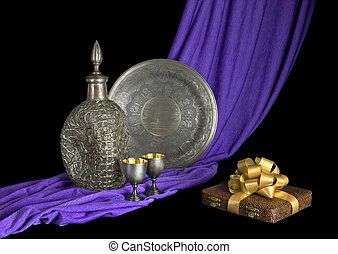 Silverware and the gift are on the draped fabric