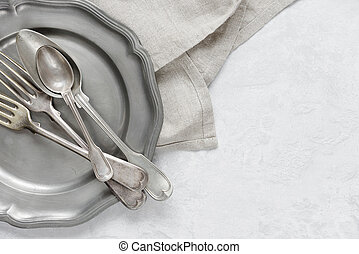 Silverware on a pewter plate - Various silverware on a...