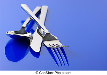 Silverware on blue - Stainless spoon, fork and knife on blue...
