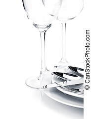 Silverware or flatware set over plates and wine glasses -...