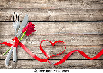 Silverware tied up with red ribbon in heart shape on wooden planks
