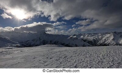 Silvretta Alps winter landscape with clouds and sun in sky and snowstorm (Austria).