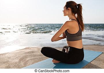 simpático, mujer joven, practicar, yoga, en, el, playa