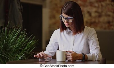 Simpatic brunette with glasses close-up. Drinks fragrant coffee and using a mobile phone dials up text messages, watches news, flips through photos, communicates in a social network.