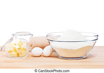 simple baking tools and ingredients on a wooden table and white background