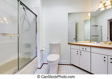 Simple bright bathroom with white cabinet and glass door shower