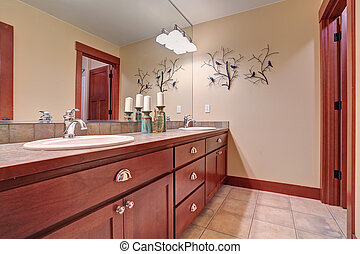 Simple bathroom with red wood cabinets.