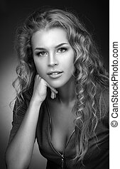 Simple black and white portrait of a beautiful young blonde with long curly hair